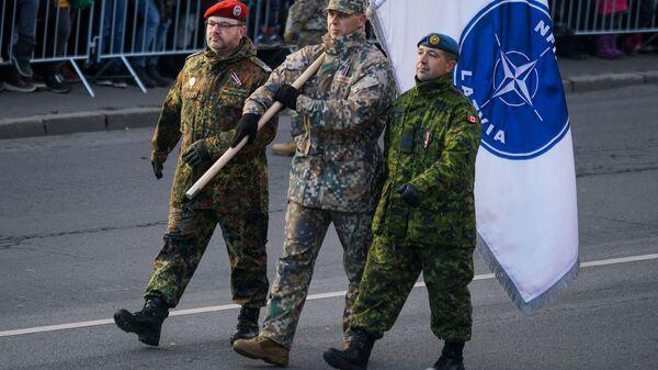 Немецкий, латвийский и канадский военные с флагом Расширенной передовой группы НАТО в Латвии - Sputnik Latvija