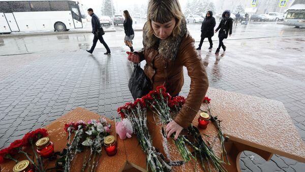 Женщина возлагает цветы у аэропорта Ростова-на-Дону - Sputnik Латвия
