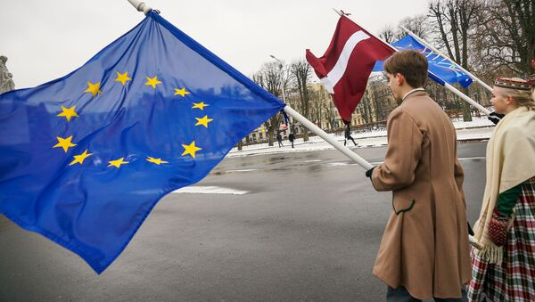 Юноша и девушка в национальных латышских костюмах с флагами ЕС и Латвии у Памятника Свободы в Риге - Sputnik Latvija