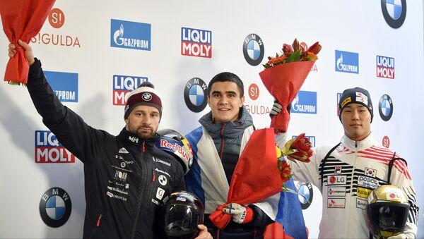Мартинс Дукурс (слева), Никита Трегубов (в центре) и Юн Сунбин (справа) во время награждения после соревнований первого этапа Кубка мира по скелетону и бобслею - Sputnik Латвия
