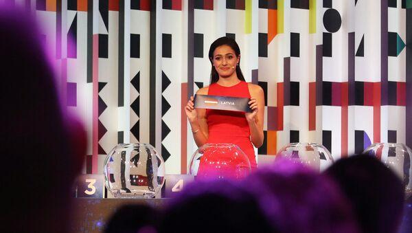 Телеведущая Люси Айюб показывает карточку Латвии во время жеребьевки полуфинала Евровидения - Sputnik Latvija