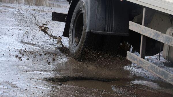 Грузовой автомобиль едет по разбитому дорожному покрытию - Sputnik Latvija