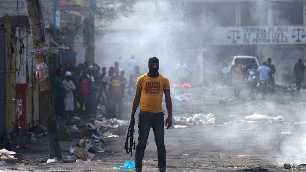 Мужчина с оружием во время антиправительственных протестов в Порт-о-Пренсе, Гаити, 17 февраля 2019 - Sputnik Латвия