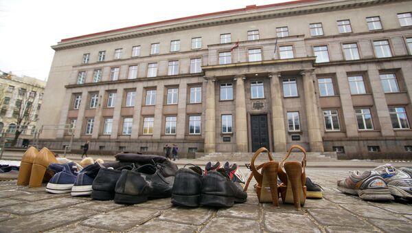 Латвийцы приносят обувь к зданию кабмина - Sputnik Latvija