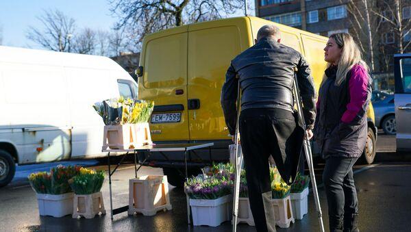 Мужчина с инвалидностью на цветочном рынке в Риге - Sputnik Латвия