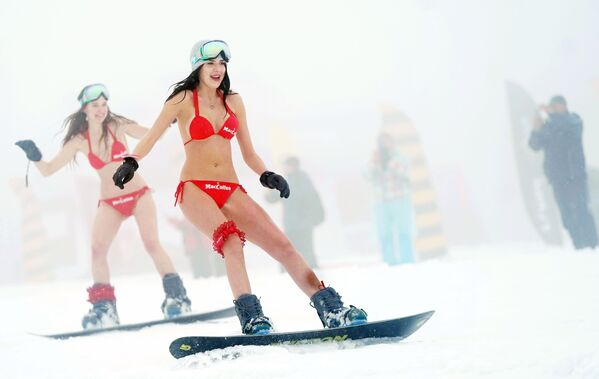Участницы высокогорного карнавала BoogelWoogel-2019 во время массового спуска с горы в купальниках на горнолыжном курорте Роза Хутор в Сочи - Sputnik Латвия