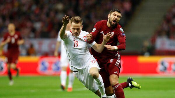 Поляк Томаш Кендзера (слева) и латвиец Артур Карашаускас в отборочном матче чемпионата Европы 2020 года - Sputnik Латвия