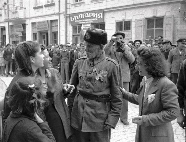 Ветеран турецкой войны беседует с девушками, в освобожденном войсками РККА от фашистов, болгарском городе, 1944 год - Sputnik Латвия