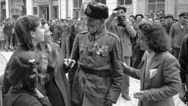 Ветеран турецкой войны беседует с девушками, в освобожденном войсками РККА от фашистов, болгарском городе, 1944 год - Sputnik Latvija