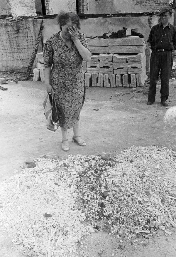 Женщина плачет у праха сожженных людей в печах лагеря смерти Майданека в польском Люблине, 1944 год - Sputnik Латвия