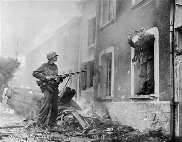 Американский солдат держит на прицеле немецкого солдата во время освобождения Франции в ходе Второй Мировой войны, 1944 год - Sputnik Латвия