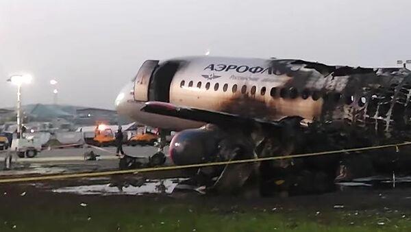 Обгоревший фюзеляж самолета компании Аэрофлот Sukhoi Superjet 100 на летном поле в аэропорту Шереметьево - Sputnik Латвия