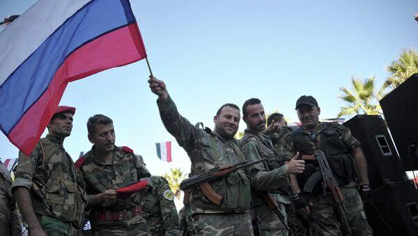Сирийские военные с российским флагом во время митинга в городе Тартус, Сирия - Sputnik Latvija