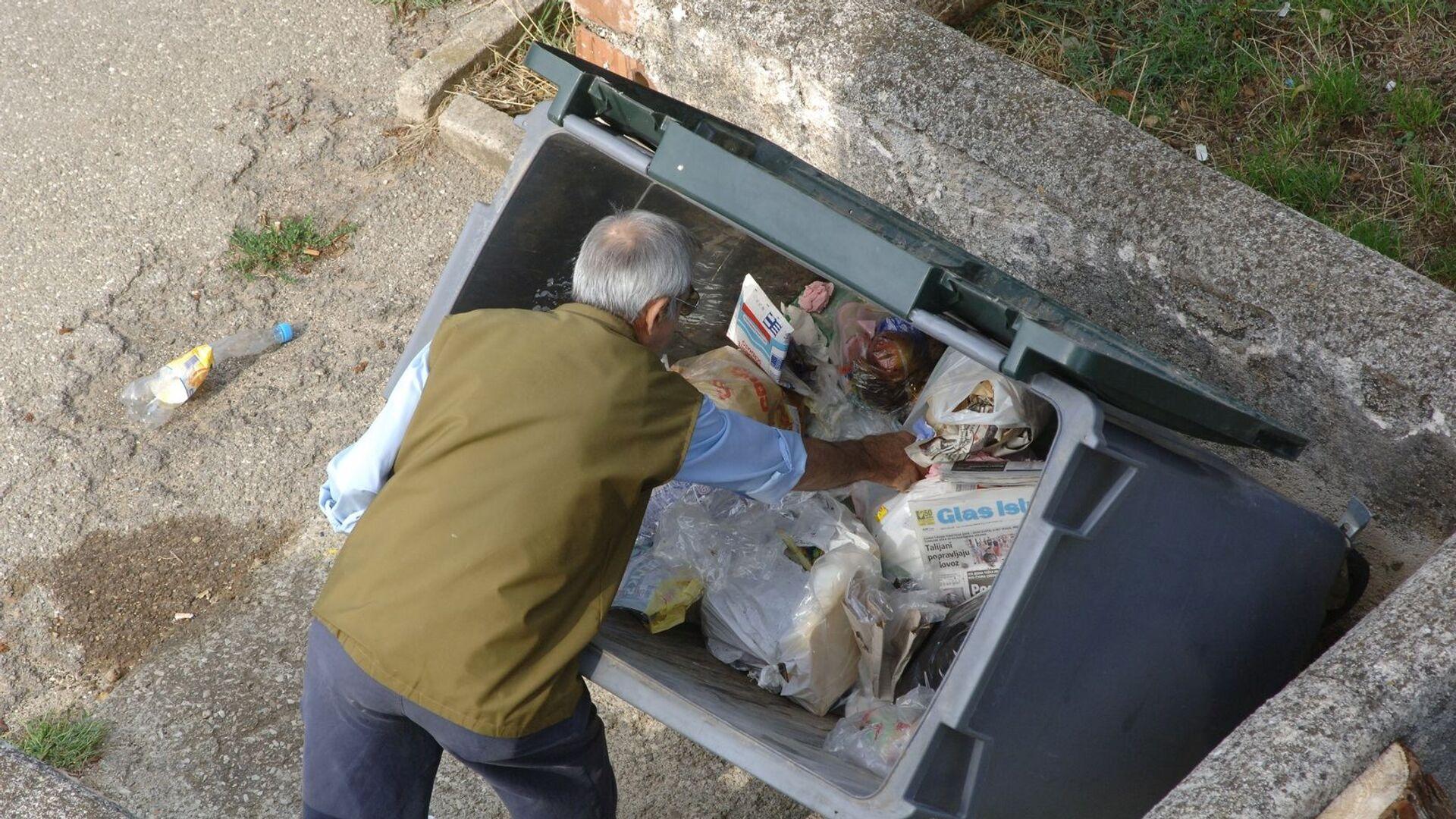 Мужчина у мусорного контейнера - Sputnik Латвия, 1920, 26.08.2021