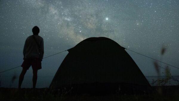 Мужчина наблюдает за звездным небом на берегу Черного моря возле поселка Морское в Крыму - Sputnik Latvija