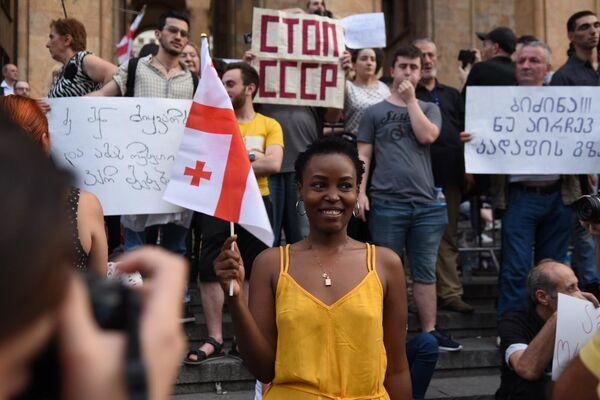 Пожалуй, это самая необычная участница митинга в Тбилиси. Подоплека ее присутствия у парламента так и осталась за кадром: то ли девушка проходила мимо и решила сфотографироваться на память, то ли действительно поддерживает акцию - Sputnik Латвия