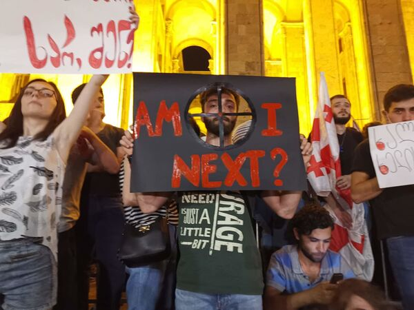 Участник митинга спрашивает: Я - следующий?, намекая на методы, которые правоохранители применили для разгона беспорядков в ночь на 21 июня - Sputnik Латвия