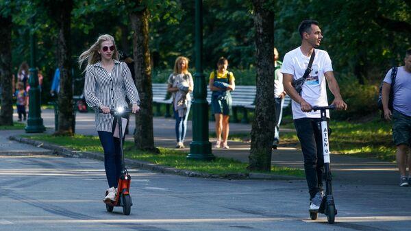Молодые люди на прокатных электросамокатах - Sputnik Латвия