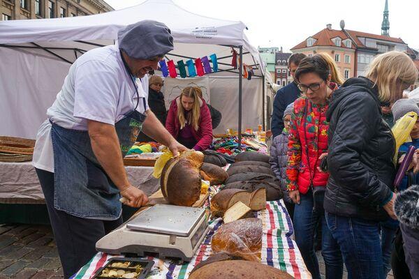 Торговцы в День Микелиса щедро нарезают хлеб  - Sputnik Латвия