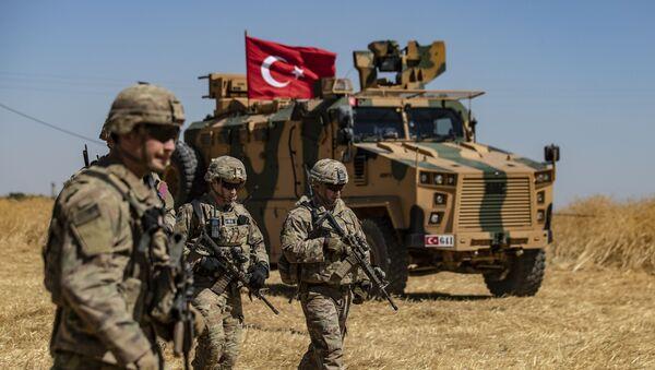 Американские солдаты проходят мимо турецкого военного спецтранспорта в Сирии - Sputnik Latvija