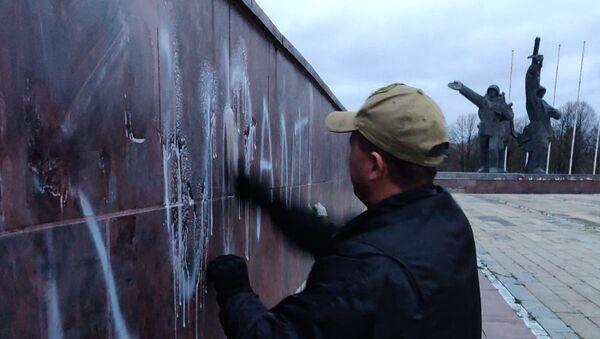 Общественник смывает надпись оккупанты с памятника Освободителям - Sputnik Latvija