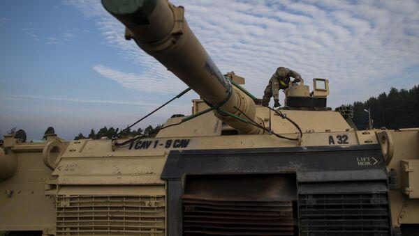 Американский военнослужащий готовит танк Abrams к разгрузке на железнодорожной станции в Литве - Sputnik Latvija