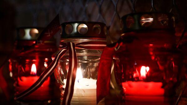 Рижане зажигают поминальные свечи у стены Рижского замка в День Лачплесиса - Sputnik Латвия