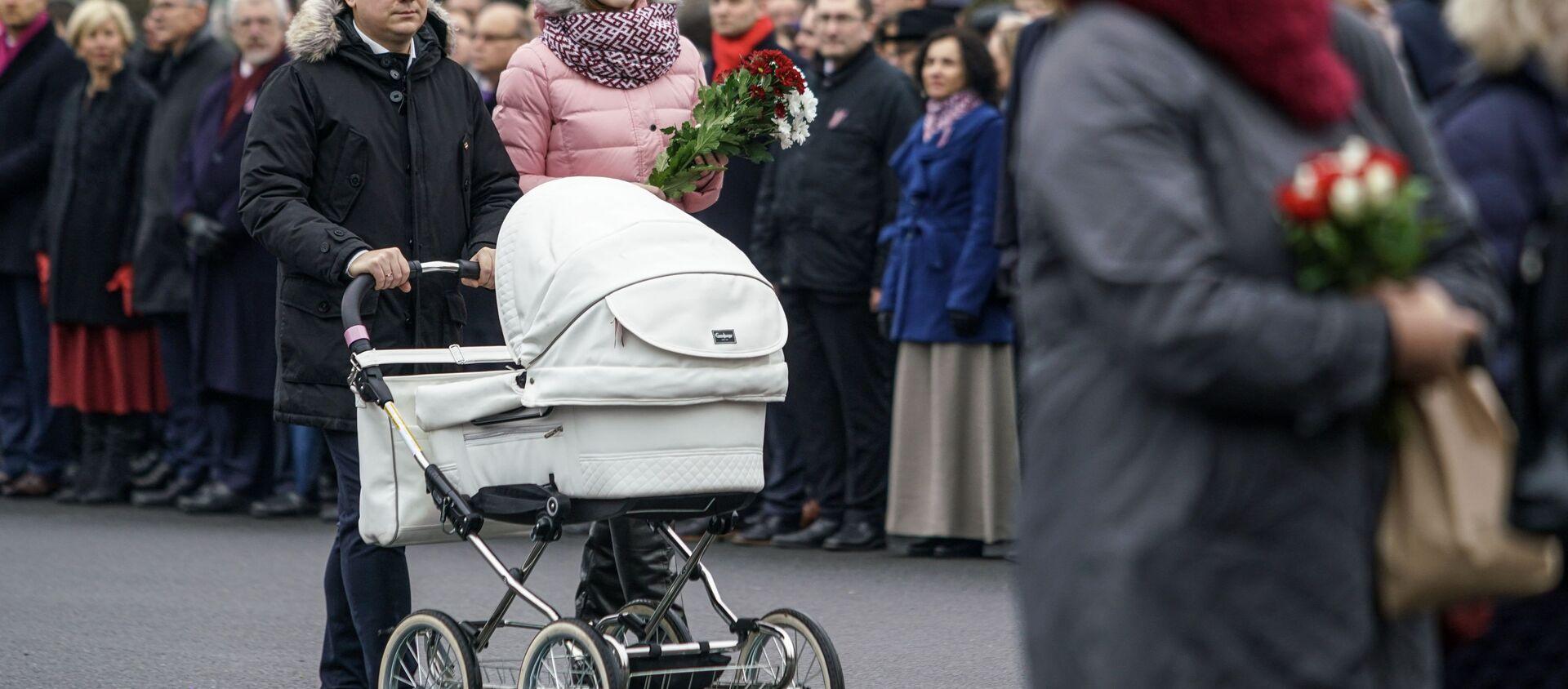 Семья с ребенком проходит к памятнику Свободы, чтобы возложить цветы - Sputnik Latvija, 1920, 31.01.2021