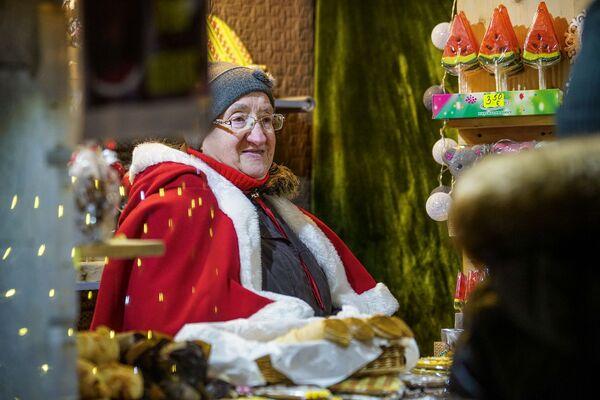 Продавщица на рождественской ярмарке на Домской площади в Риге. - Sputnik Латвия