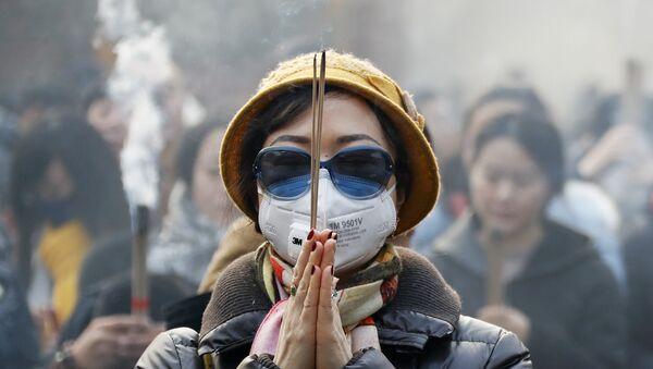 Женщина в маске и солнцезащитных очках во время молитвы в первый день Нового года в Пекине - Sputnik Латвия