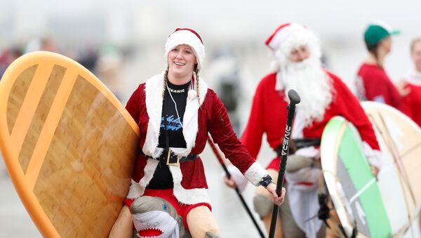 Участники ежегодного заплыва серферов в костюмах Санта-Клауса в США  - Sputnik Latvija