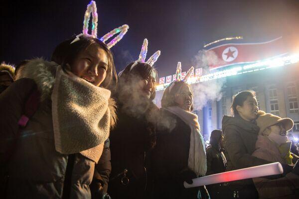 Девушки смотрят запуск салюта во время празднования Нового года в КНДР  - Sputnik Латвия