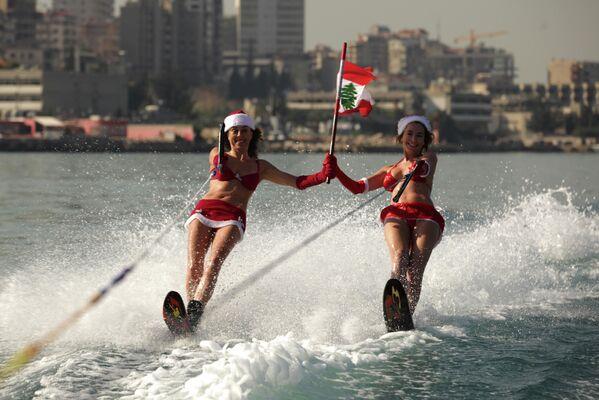 Две девушки в костюме Санта-Клауса во время катания на водных лыжах в Ливане  - Sputnik Латвия