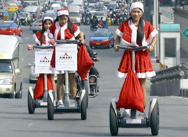 Работницы отеля в костюмах Санта-Клауса во время раздачи подарков в Бангкоке  - Sputnik Латвия
