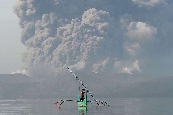 Молодой рыбак на каноэ у подножия вулкана Таал, извергающего пепел, к югу от Манилы - Sputnik Латвия
