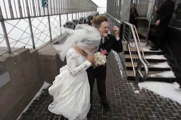 Молодожены во время сильного ветра на обзорной площадке Эмпайр-стейт-билдинга в Нью-Йорке  - Sputnik Латвия