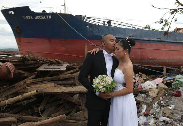Жених Эрвин Нирва целует свою невесту Ризу на фоне разрушенных тайфуном домов и корабля на Филиппинах - Sputnik Латвия