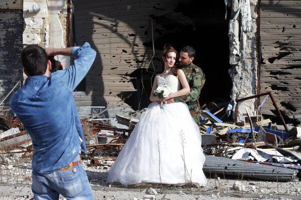 Сирийские молодожены во время фотосессии на фоне разрушенных зданий в Хомсе  - Sputnik Латвия