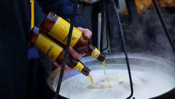 Пиво разогревали в котле, прямо на костре, превращая его в согревающий напиток. Четвертый фестиваль уличной еды Street Food Festival в Риге. - Sputnik Латвия