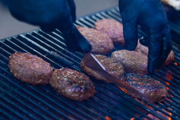 Сочные говяжьи котлеты для бургеров на  фестивале уличной еды Street Food Festival в Риге готовят на гриле. - Sputnik Латвия