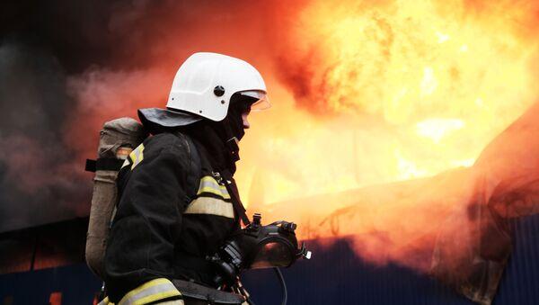 Сотрудник МЧС во время тушения пожара - Sputnik Latvija