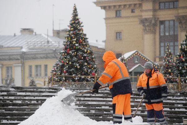 Сотрудники коммунальной службы чистят тротуары от снега в Москве - Sputnik Латвия