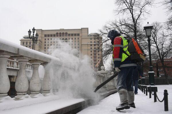 Сотрудник коммунальной службы чистит парапет у Александровского сада в Москве от снега - Sputnik Латвия