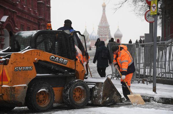 Сотрудники коммунальной службы чистят тротуар от снега в Москве - Sputnik Латвия