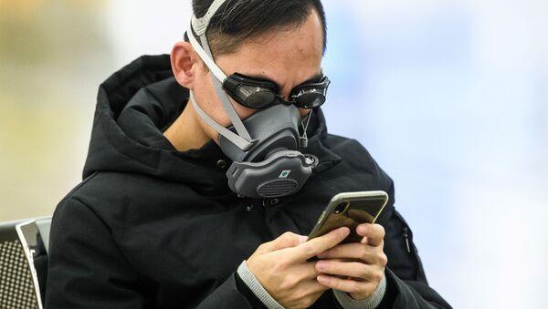 Пассажир в очках для плавания и маске на железнодорожной станции в Гонконге - Sputnik Latvija