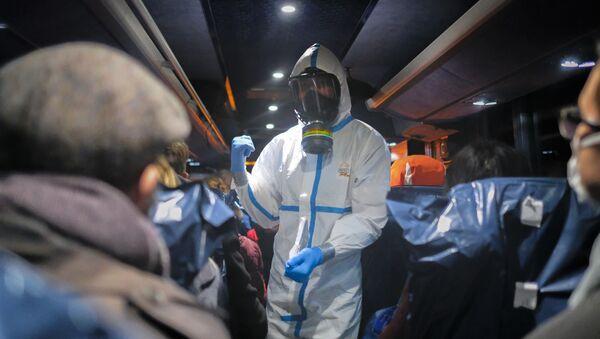 Офицер в защитной одежде инструктирует эвакуированных из Ухани, Китай - Sputnik Latvija