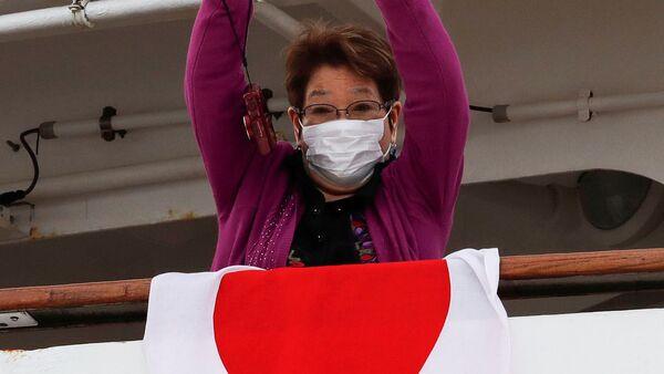 Пассажирка в медицинской маске на борту круизного лайнера Diamond Princes, помещенного в карантин у японского порта Йокогама - Sputnik Латвия