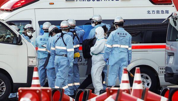 Пожарные в защитных костюмах помещают в машину скорой помощи заболевших пассажиров круизного лайнера Diamond Princes, помещенного в карантин у японского порта Йокогама - Sputnik Latvija