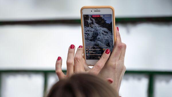 Женщина фотографирует замерзший стометровый водопад Учан-Су в Крыму - Sputnik Латвия