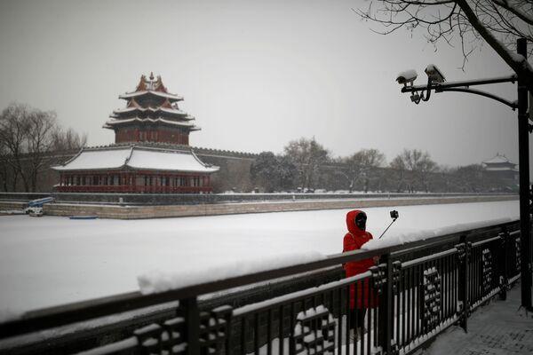 Туристов и местных жителей на улицах почти нет. Девушка в маске во время селфи у Запретного города в Пекине  - Sputnik Латвия
